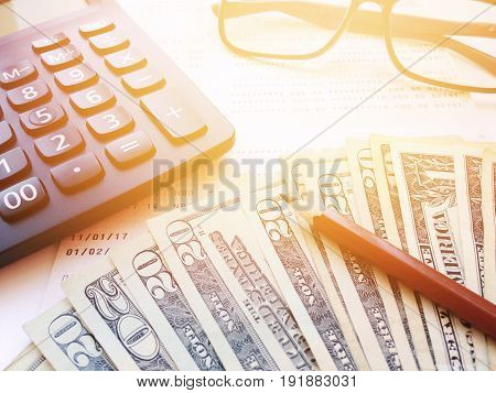Business, finance, savings, banking or  loan concept : Pencil, eyeglasses, calculator, money and savings account passbook or financial statement on white background
