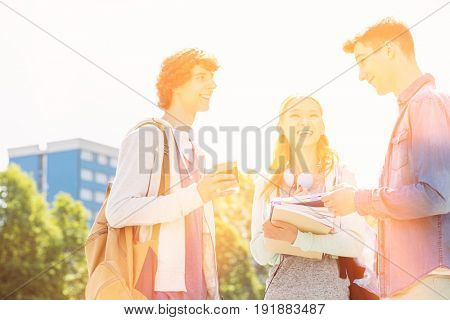 Happy university students conversing at campus