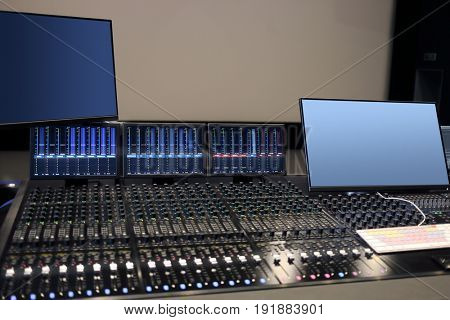 Empty modern recording studio with special equipment, cinema display out of focus