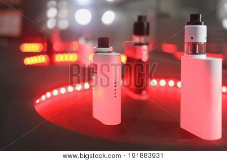 Electronic Cigarettes are on table with red illumination, shallow dof