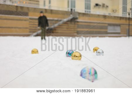 Six balls for petanque game on snow and boy out of focus outdoor at winter day
