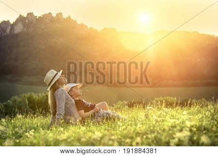 Happiness mother and son seating on the green grass around mountains under sunlight on sunny day