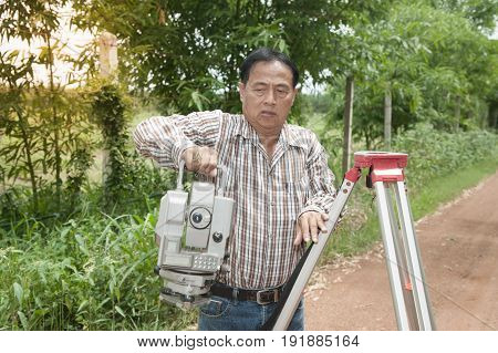 Surveyor or Engineer keep Theodolite when work finished on the street in a field.