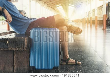 Backpack and luggage at the train station with a traveler. Travel concept.