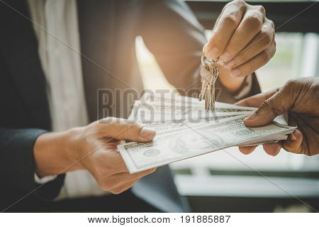 Hands Of Estate Agent Giving Keys To The Customer And Bank Note Completed Deal With Vintage Filter E