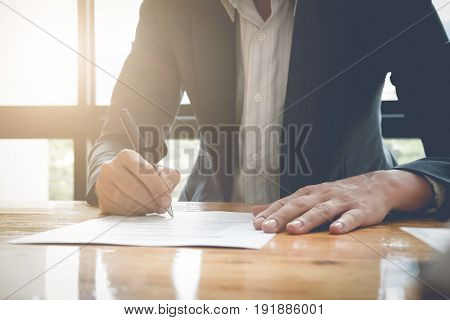 Close-up Of Businessman Signing Contract Paper With Pen, Vintage Filter Effect