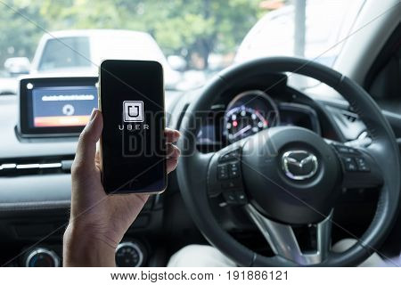 Chiang Mai,thailand - June 15, 2017 : A Man Hand Holding Uber App Showing On Iphone 6S On Road And B