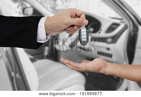 Hand holding car key remote, with modern car backgrounds