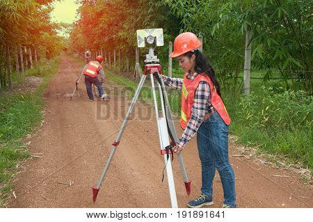 Surveyor or Engineer making measure by Theodolite and prism reflector with partner on the street in a field.