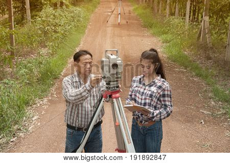 Surveyor or Engineer making measure by Theodolite with partner on the street in a field.