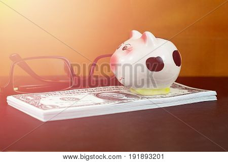 Small piggy bank on piles of US dollar banknotes and brown glasses on black floor for money saving concept