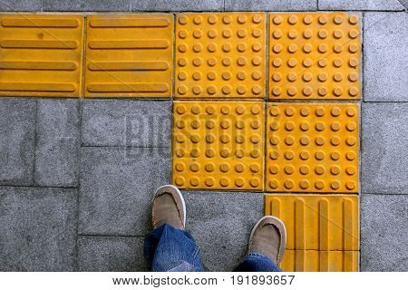 shoes on block tactile paving for blind handicap on tiles pathway walkway for blindness people.
