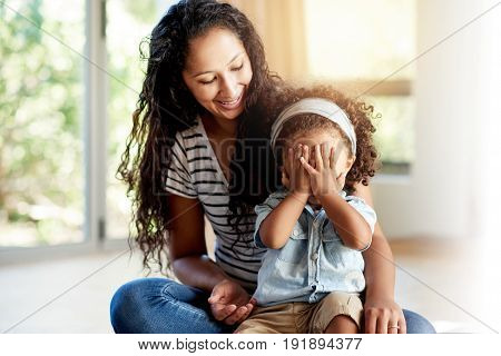 Black Woman With Daughter Hiding Face Sitting On Floor