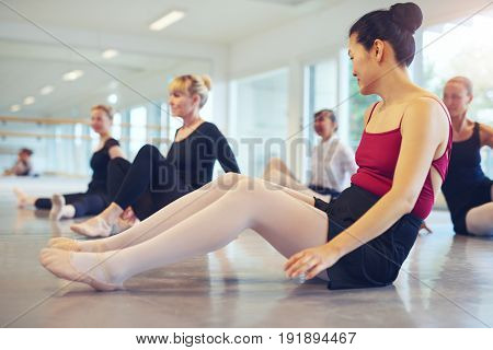 Group of ballerinas sitting on the floor during the lesson in ballet class.