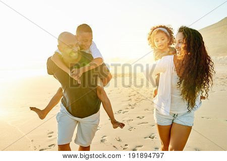 Cheerful black man and woman walking and carrying their children in evening sandy shore.