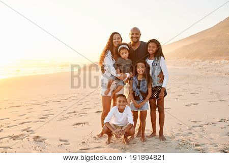 Cheerful African-American man and woman standing on beach with their kids and smiling together.