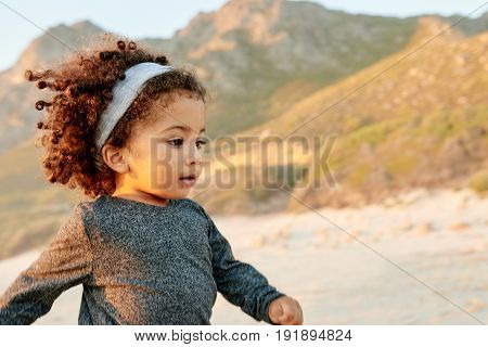 Adorable small African-American curly girl running and looking away on sandy shore.
