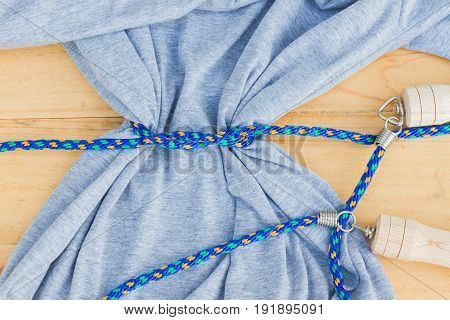 gray t-shirt pressed a blue jump rope diet or healthy concept