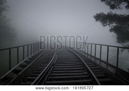 Rail tracks on a bridge in the fog with some trees and handrails