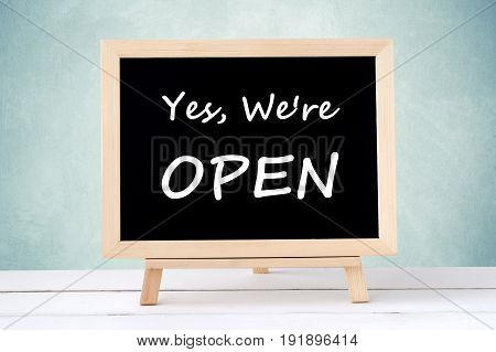 Yes we' re open on blackboard over green wall background business hours sign