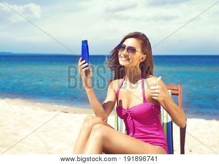 A young woman in a swimsuit adding suntan on the beach