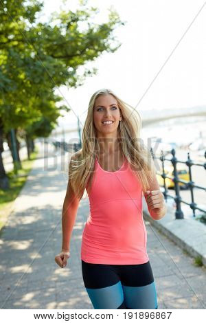 Happy blonde female runner training outdoors.