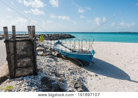 Boat in Maafushi Island with crystal clear water in the beach Maldives.