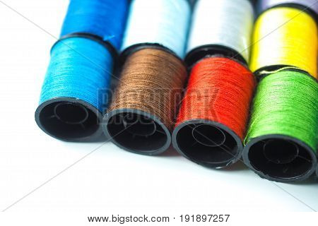 Colorful thread reels on white background, selective focus