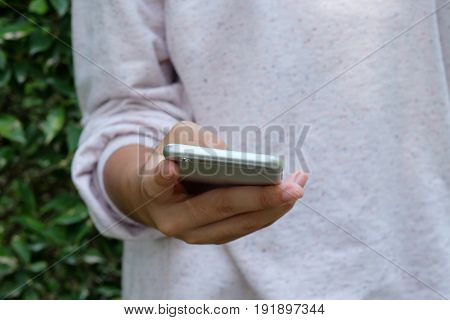 Woman hand using smart phone on green park background business and technology concept gen Z digital marketing lifestyle the internet of things social media network