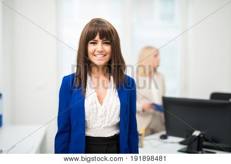 Smiling young woman in her office