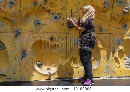 Labuan,Malaysia-May 21,2017:Happy muslim woman with safety equipment climb ready to climbing wall in Labuan,Malaysia.Rock climbing is a fun & exciting activity suitable for all the family