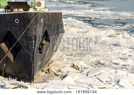 Boat in ice. Boat stuck in ice of frozen river. Danube river, Novi Sad, Serbia. Winter image.