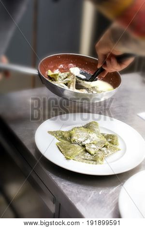 Chef Plating Up A Serving Of Ravioli Pasta