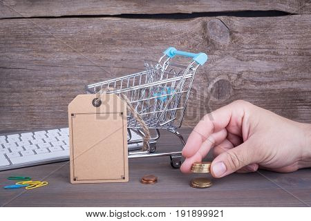 E-commerce concept. Purchasing cart with a blank price tag on a dark wooden background.