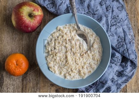 Oatmeal porridge in bowl for breakfast on rustic wooden table