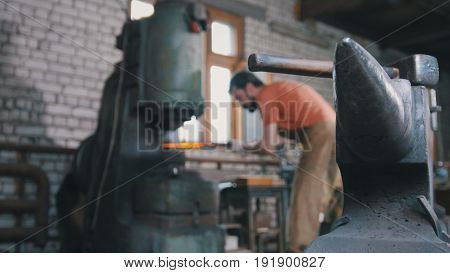 Blacksmith with a beard substitutes a red-hot metal piece for an automatic hammer