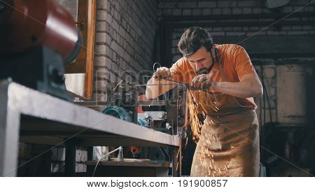 Blacksmith with a beard and work clothes makes a grinding of a metal product