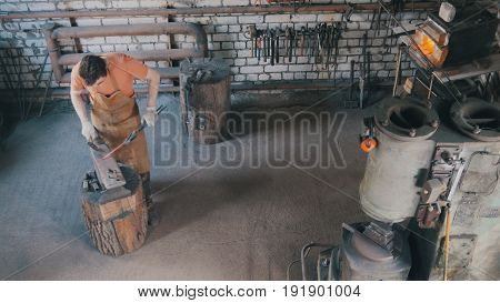 Beard man blacksmith in forge makes metal tools on iron anvil with hammer, top view, small business