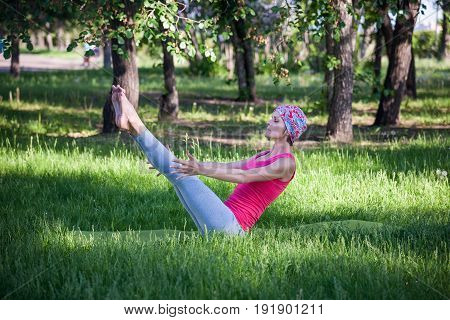 young woman doing yoga and gymnastics in the Park. Yoga in the Park, outdoors , women's health, Yoga woman. The concept of healthy lifestyle and recreation. boat pose.