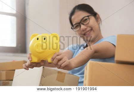 Young Asian woman holding yellow piggy bank. Own business