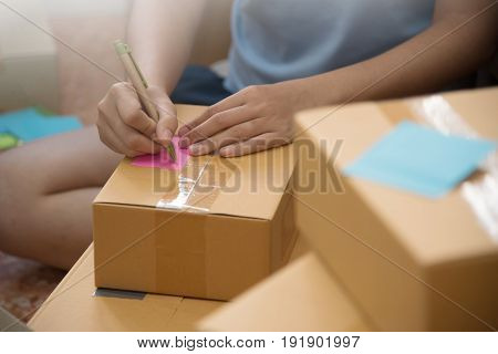 Close up Asian woman checking supplies and writing on cardboard box in her small warehouse. Own business