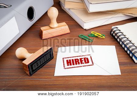 Hired. Rubber Stamp on desk in the Office.