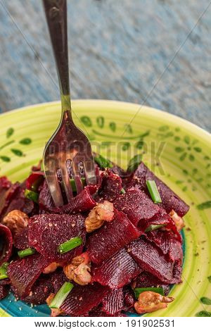 On a bright ethnic plate is a vegetarian lean beet salad green shnit-onion gritsy nut. Top view. The concept of simple healthy food.