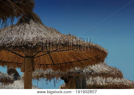 Parasol made of straw or sugar cane produced. Beach sun protection in the background a cloudless blue sky.