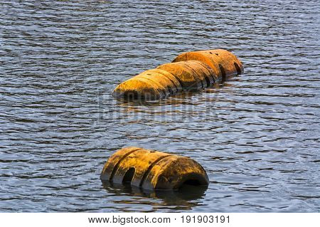 Buoy pipeline or plastic floats float on the water surface.