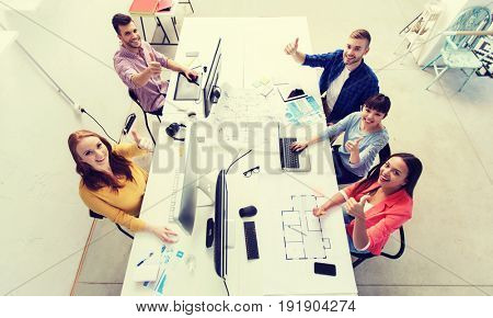 business, startup, success and people concept - creative team with computers, blueprint and scheme showing thumbs up at office
