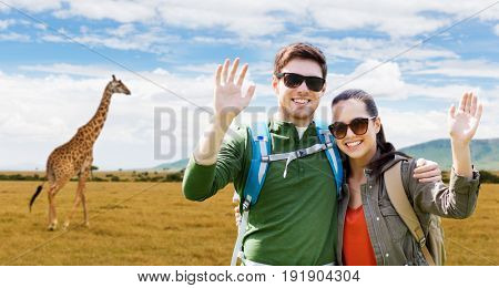 travel, hiking, backpacking, tourism and people concept - happy couple with backpacks waving hands over african savannah and giraffe background