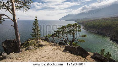 The landscape is mountainous coast of lake Baikal in the horizon.