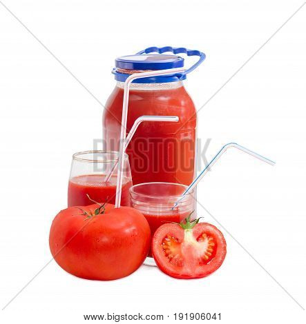 Big fresh whole tomato with bendable drinking straw inserted into it half of the tomato tomato juice in glass jar and in two different glasses with drinking straws on a light background