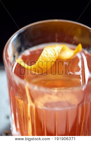 alcohol drinks and luxury concept - close up of glass with orange cocktail at bar